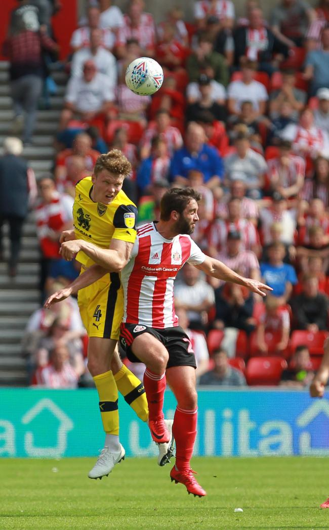 Rob Dickie beats Will Grigg in an aerial battle on Saturday       Picture: Richard Parkes