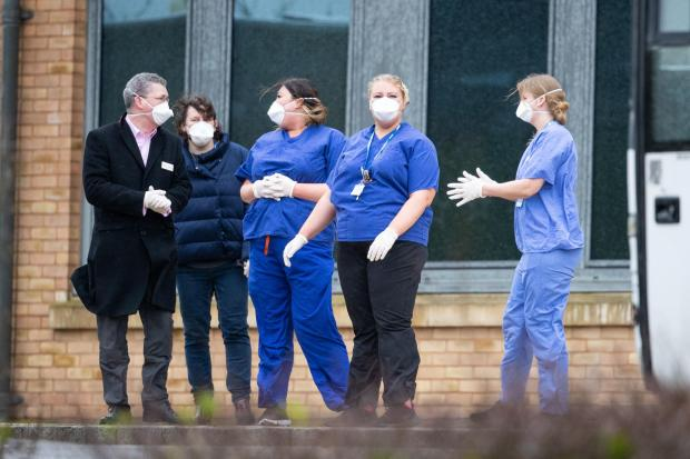 Witney Gazette: Members of staff wait as coaches carrying Coronavirus evacuees arrive at Kents Hill Park Training and Conference Centre, in Milton Keynes. Picture: Aaron Chown/PA