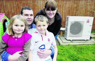Mark and Hayley Pearce and their two children Amber, eight, and James, 10, with the outdoor section of the heat pump