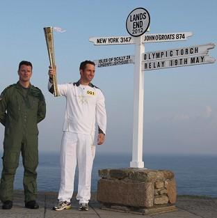 Ben Ainslie holds the Olympic Torch as he begins the first leg of the relay (Chris Radburn/LOCOG/PA Wire)
