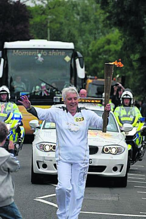 Grandmother Mo Merchant carries the Olympic torch through Nettlebed