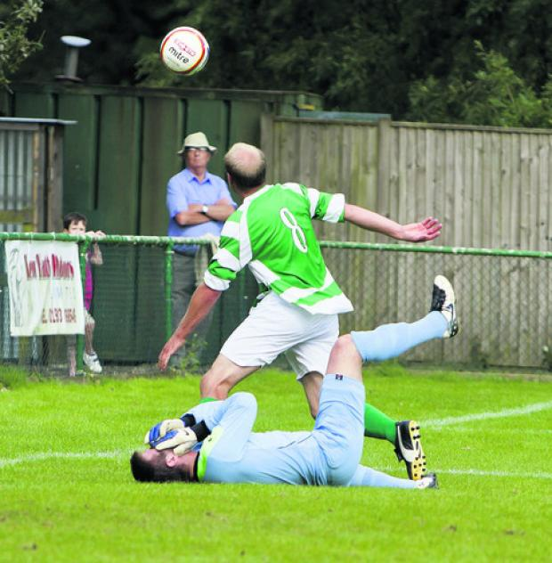 North Leigh's Sam Warrell holds his head in agony following a collision with Wantage's Tom Rowe that left the keeper with a nasty gash