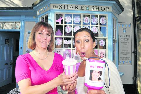 Debbie Shake, of the Shake Shop, hands a pink milkshake to TV presenter Saira Khan