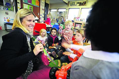 Cassington Pre-School fundraiser, Julie Bignone reads to children in the pre-school's temporary building