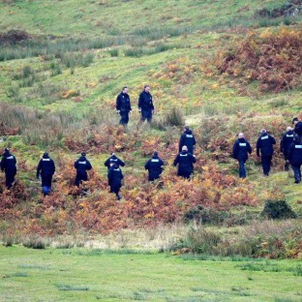 A police team searches land near Machynlleth, Mid Wales, for five-year-old April Jones