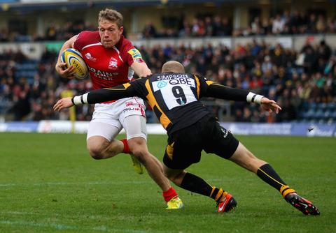 London Welsh's Phil Mackenzie hands off Wasps' scrum half Joe Simpson