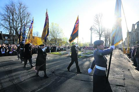 Standard bearers lead the parade past Witney's war memorial, in Church Green