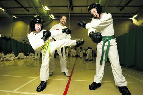 Taekwondo teacher Ciaran McDonald with Isobel Hodson, nine, and Sean McIntyre, 13
