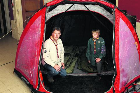 Witney Gazette: Minster Lovell scout leader Angus Campbell and his son, Ryan, 12 with the one tent left behind by burglars