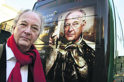 Philip Pullman, with an Oxford bus bearing his likeness