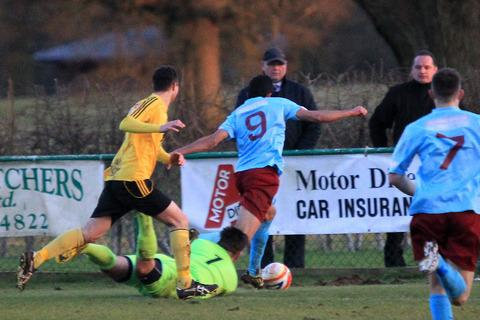North Leigh keeper Sam Warrell brings down Taunton Town forward Khaled Badavi inside the penalty area