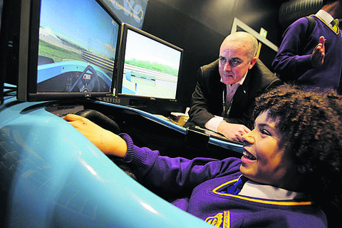 Andy Thomas, head of engineering at Oxford and Cherwell Valley College, which is taking part in the fair as a training provider, watches as Oxford Spires Academy student Jamie Cummins, 13, tries a racing simulator at last year's event
