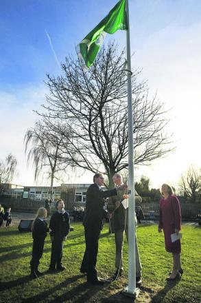 The Duke, second right, raises the flag, watched by, from left, pupils Tabitha Ward and Matthew Culligan, chairman of governors Darrell Marchand and headteacher Lisa Rowe