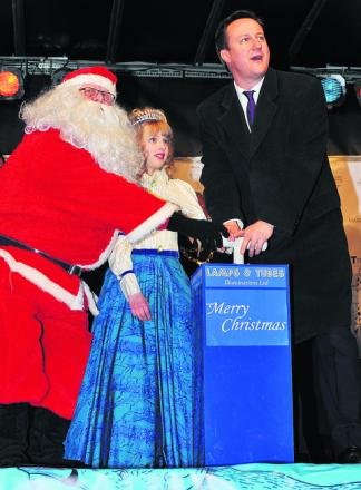David Cameron helps Father Christmas and Winter Princess Catherine Newett, 10, switch on Witney's Christmas lights in 2011