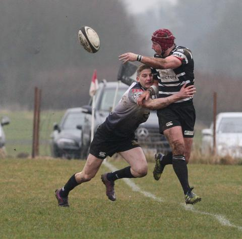 Chinnor centre Sam Stoop gets the ball away under pressure against Dings Crusaders, but his side could not hold on for victory