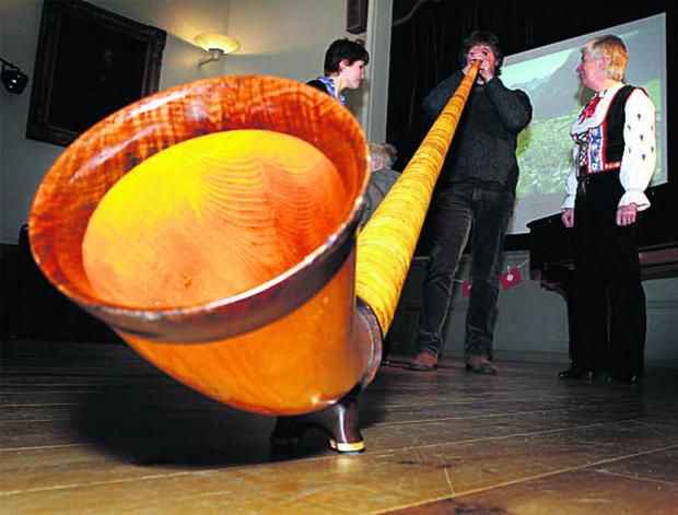 Simon Mead tries to play an alphorn, watched by his daughter Esther, left, and musician Frances Jones