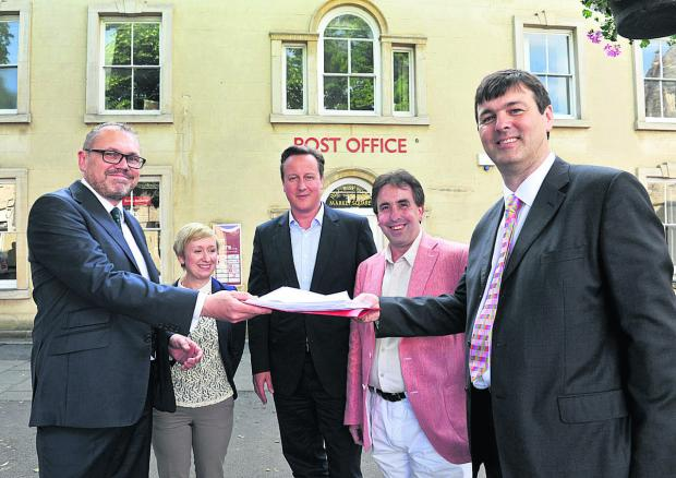 Mark Davies, the communications director of the Post Office, left, recieves the petition from Duncan Enright, right, watched by, from left, Labour county councillor Laura Price, David Cameron and Richard Langridge