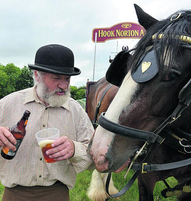 Witney Gazette: Roger Hughes from Hook Norton Ales pours a beer for Major the Horse. Picture:  Simon Williams