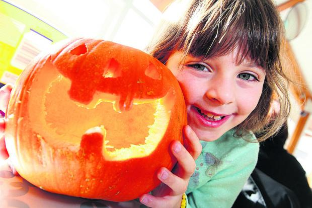 Witney Gazette: Lucie Doggett, seven, with a pumpkin lantern she made at Blenheim Palace