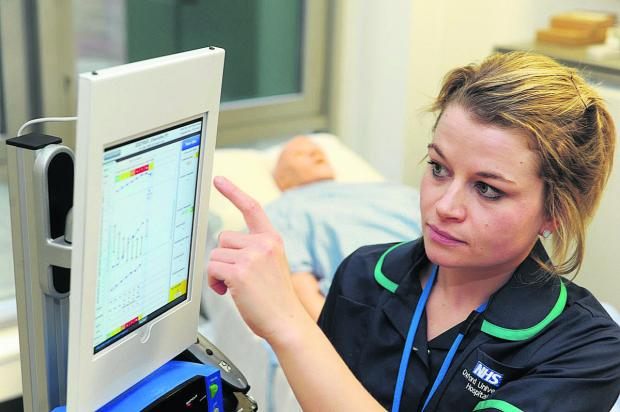 Witney Gazette: Nurse Julia Knight at Oxford's John Radcliffe Hospital tries out the new iPad-based early warning system for patient monitoring  Picture: OX64145 Jon Lewis