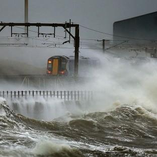 Witney Gazette: A train is lashed by waves along the coast at Saltcoats as Scotland has been warned to expect a storm surge.