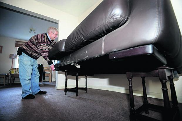 Witney Gazette: Andrew Ivett checks his sofa placed on tables as flood waters rise around his home in Earl Street