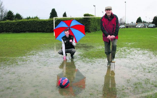 Witney Gazette: Hanborough chairman and groundsman Ray Keylock (right) and his grandson and player Craig Keylock, survey the scene ahead of the abandoned Oxfordshire John Fathers Junior Shield tie with Carterton Rangers