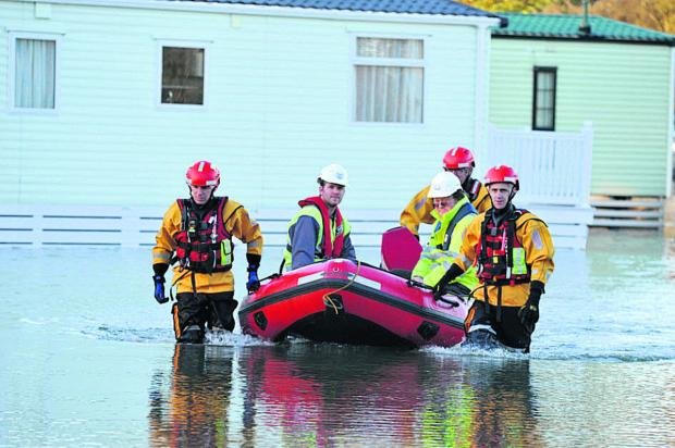 Witney Gazette: Fire and Rescue staff escort Thames Water engineers back from fixing a pumping station at Bablockhythe