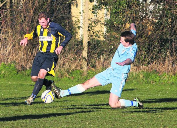 Eynsham's Tom Smith (right) beats Glen Willett to the ball during their 4-0 win at Hanborough Res in Division 1 on Saturday