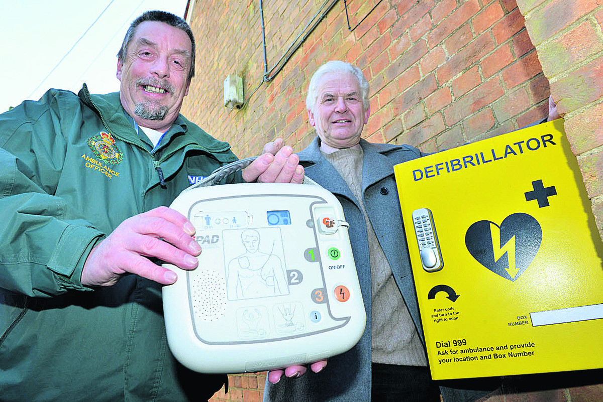 Dick Tracey, of South Central Ambulance Service, left, and Michael Green, vice-chairman of Combe Parish Council with the defibrillator installed at the village's Reading Room