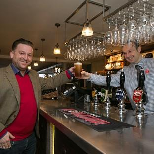 Witney Gazette: Tom from Beaconsfield, left, buys the first pint from shift manager Derek at the new JD Wetherspoon pub called Hope And Champion at the M40 services at Beaconsfield