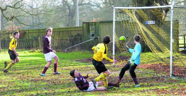 Ryan Holmes (15) scores one of North Leigh's goals in their 11-1 home win against Bourton Rovers Juniors in the Under 14 A League encounter, despite a strong challenge from a home defender
