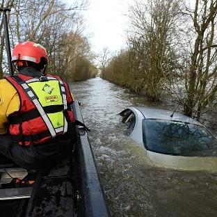Witney Gazette: Members of the Avon and Somerset Police Underwater Search Unit inspect a submerged car near Muchelney in Somerset