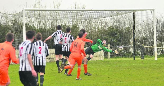 Minster Lovell's Stephen Burke (hidden) sees his shot fly into the goal, despite the efforts of Chipping Norton keeper Guy Smith