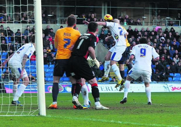 Witney Gazette: Tom Newey (virtually hidden) gets his head on Danny Rose's corner to put Oxford ahead against Wimbledon – his first goal for 210 games