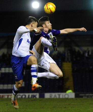 Oxford United's Deane Smalley leaps high for a header at Bury