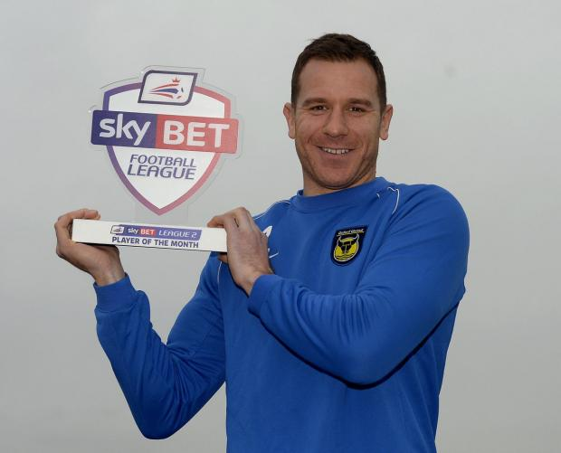 Ryan Clarke proudly displays his Sky Bet League Two player of the month trophy for January