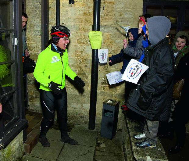 Witney Gazette: Davina McCall is greeted by cheering children at Killingworth Castle, Wootton, after she arrived for a stop during her Sport Relief challenge