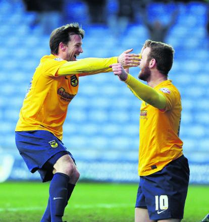 A delighted David Connolly (left) is all smiles as he congratulates Deane Smalley on scoring Oxford United's third goal in the 3-0 win over Mansfield Town at the Kassam Stadium on Saturday