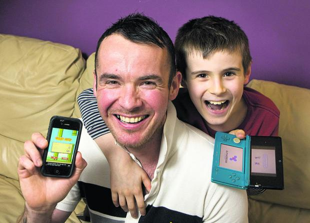 Witney Gazette: Scott Prior with his iPhone featuring the Flappy Bird app and his son Jake, who now prefers playing on his Nintendo 3DS