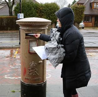 Witney Gazette: A lady uses a postbox that has been painted gold by vandals in West Kingsdown, Kent