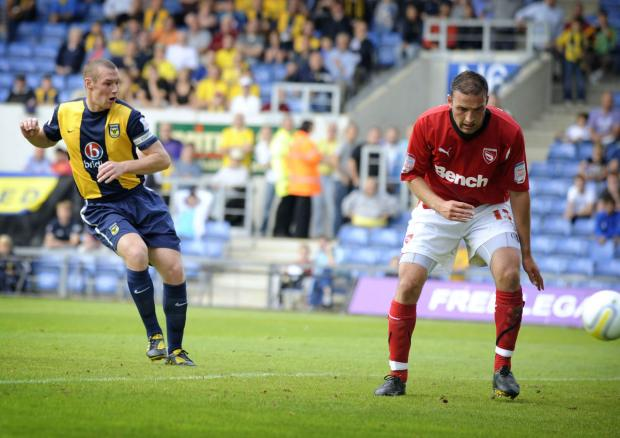 James Constable fires home his hat-trick goal against Morecambe at the Kassam Stadium