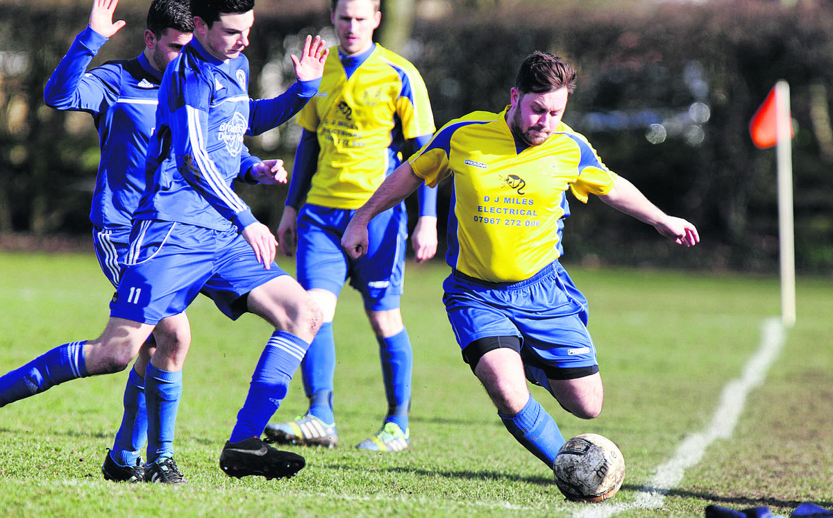Ducklington's Dan Malony makes a clearance as Jack Kennedy closes in