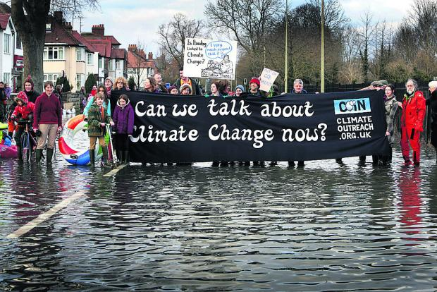 Witney Gazette: TIMELY: A flash mob raises concerns about climate change with a demonstration at flooded Abingdon Road, Oxford, last month