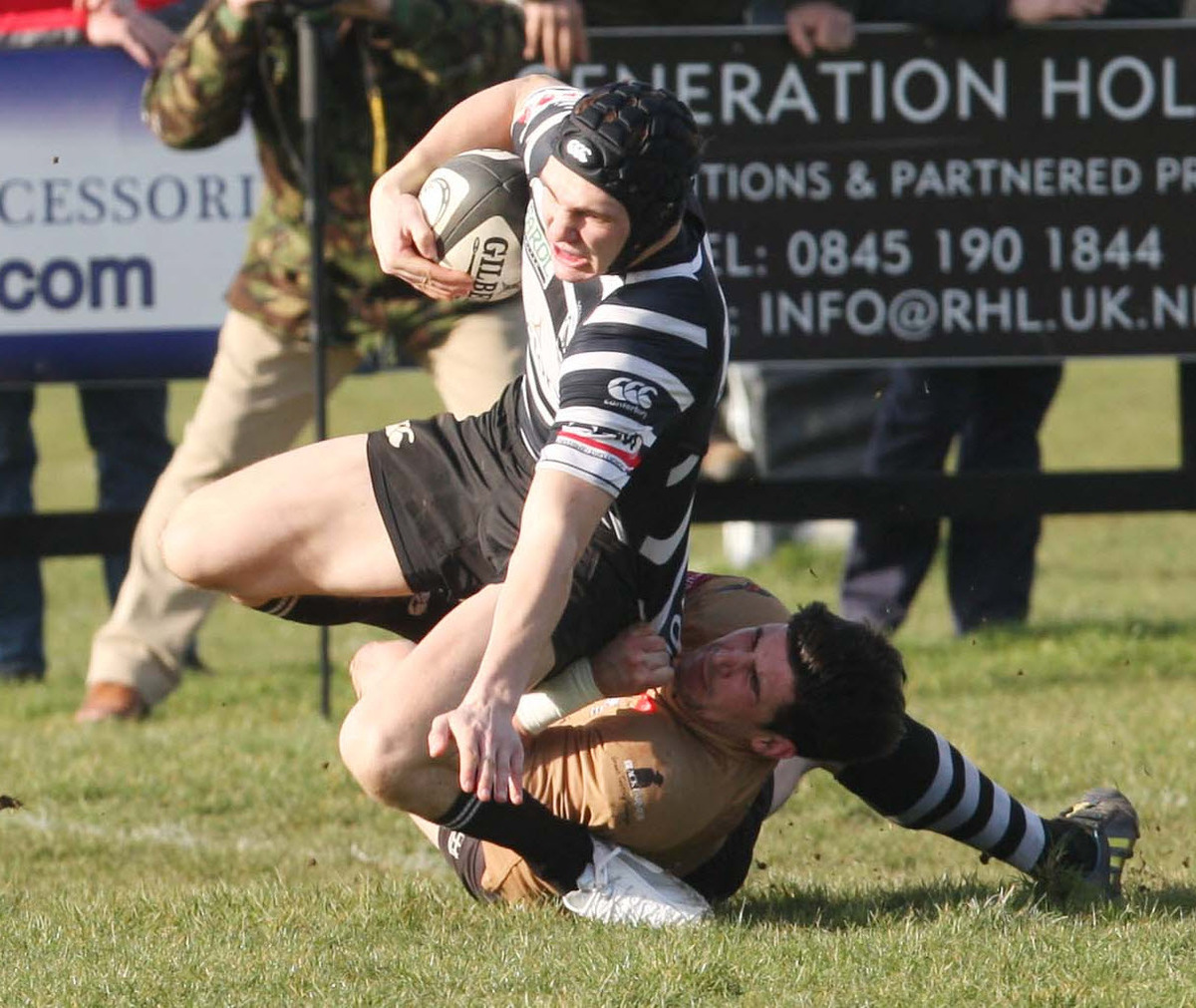 Chinnor wing George Blewitt beats Launceston's Jake Murphy  to score the first of his try double