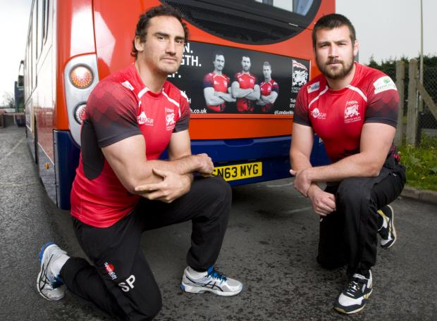 Witney Gazette: Sonny Parker (left) and club captain Matt Corker, who returns from a heart problem tomorrow, pose alongside their faces on the London Welsh's advert which also features Tom May and is appearing on Stagecoach buses in Oxfordshire