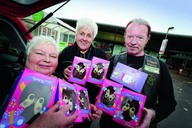 Witney Gazette: CHOC FULL: Bikers Christine, left, and George Earl of the Caldarium MCC collect Easter eggs donated by the Co-op for their May Easter egg run. Helping them load the eggs is Rita Wighton from the Co-op, in Carterton