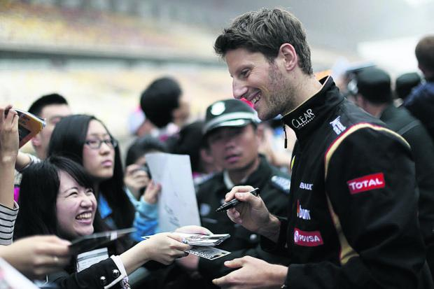 Romain Grosjean signs autographs before the Chinese Grand Prix where he was forced to retire early