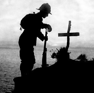 Witney Gazette: A soldier pays his respects at the grave of a colleague near Cape Helles, where the Gallipoli landings took place
