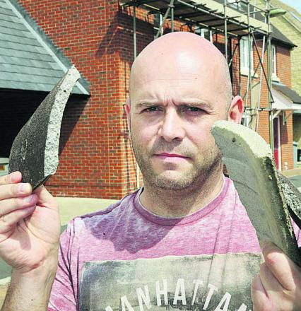 Darren Hadland with some of the tiles that fell from his roof